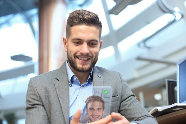 未来のコンセプトの透明な電話、彼の友人とビデオ通話をしている白人のビジネスマン