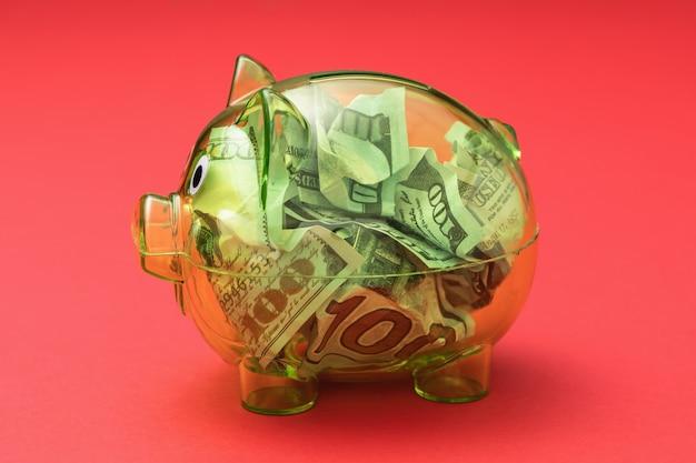 赤い表面にドルでいっぱいの透明な貯金箱