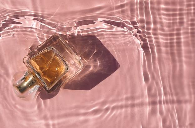Прозрачный розовый флакон духов в розовой воде с тенями вид сверху и копией пространства