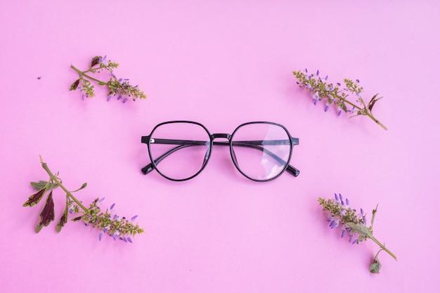 花のアクセサリーとパステルピンクの紙の背景に透明なピンクの眼鏡 Premium写真