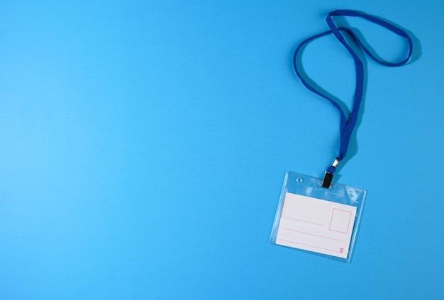 Прозрачный пластиковый значок на синем шнурке на синей поверхности, копией пространства