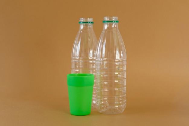 밝은 갈색 배경에 투명 플라스틱 우유 병 및 녹색 유리