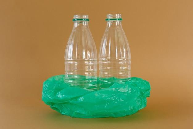 Transparent plastic milk bottles in green plastic bag on light brown background