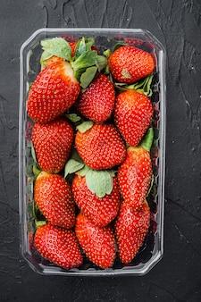 투명 플라스틱 트레이, 갓 고른 딸기, 검정색 배경, 평면도 평면 배치