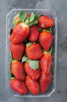 회색 배경에 갓 고른 딸기와 함께 투명한 플라스틱 트레이, 평면도 평면 누워