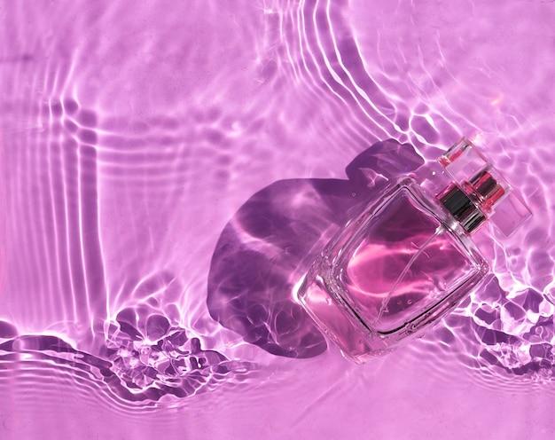 그림자와 함께 분홍색 물에 투명 보라색 병 향수