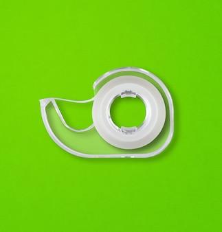 緑のテーブルに分離された透明なスコッチテープディスペンサー