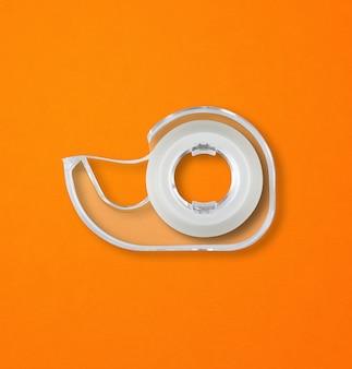 オレンジ色の表面に分離された透明なスコッチテープディスペンサー