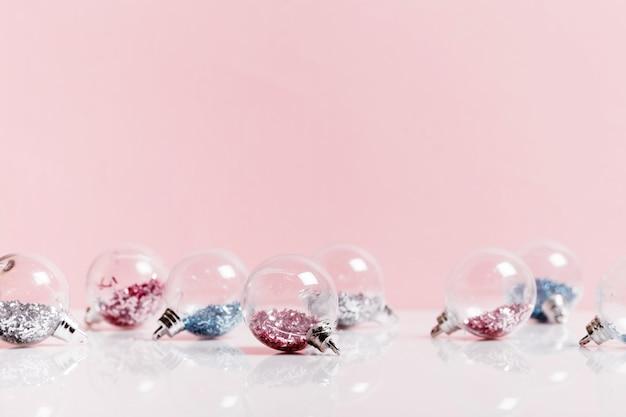Прозрачные блестки розовые и синие новогодние шары на розовом фоне. рождественский праздник композиция