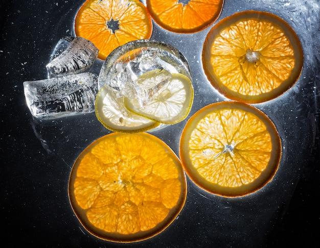 Transparent slices of oranges and lemons on the glass