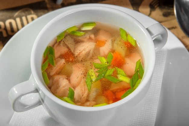 Transparent soup with chicken, carrots and greens