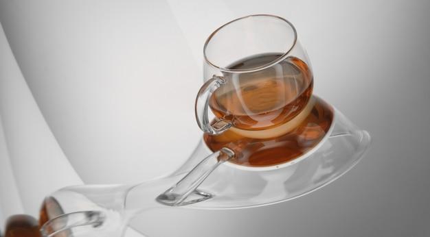 Прозрачная чашка чая на светоотражающей поверхности на светло-сером фоне. искаженное отражение