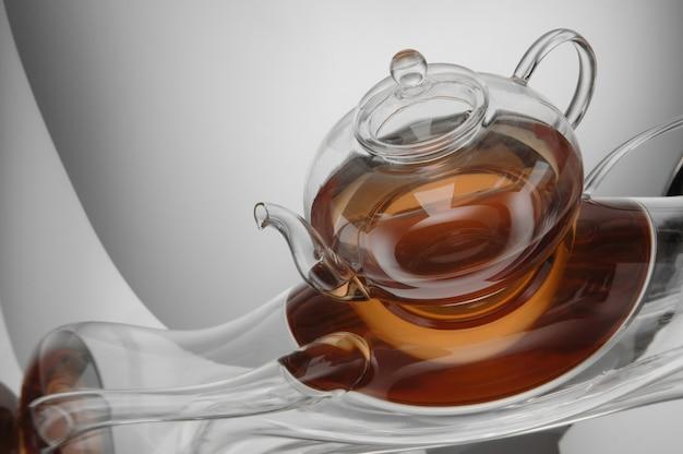 Прозрачный чайник с чаем на светоотражающей поверхности на светло-сером фоне