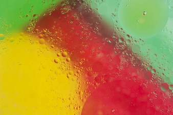 Transparent water drop over the red; yellow and green backdrop
