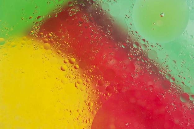 赤の上の透明な水滴。黄色と緑の背景