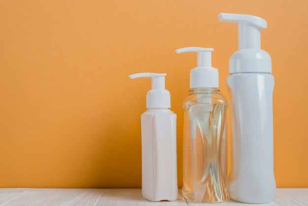 Transparent and white soap dispenser bottles against an orange background