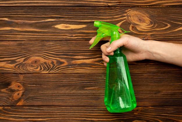 Прозрачная бутылка с водой, брызги в женских руках на деревянный стол. уборка