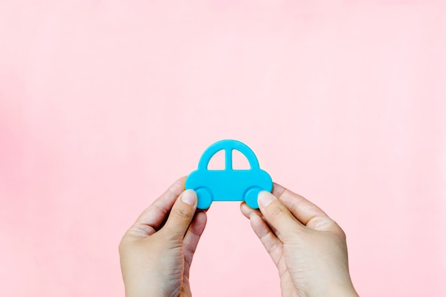 Transport, the car in hands on a pink background
