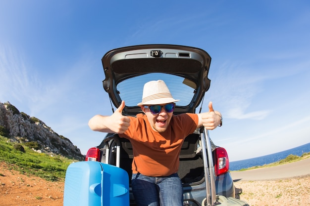 Transport, leisure, road trip and people concept. happy man enjoying road trip and summer vacation.