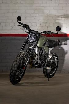 Транспортный гоночный мотоцикл зеленый на фоне кирпичной стены