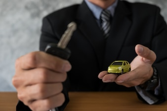 Transportation and ownership concept - customer and salesman with car key