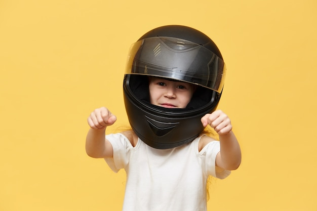 Transportation, extreme, motorsports and activity concept. portrait of dangerous little girl rider in black protective motorcycle helmet keeping hands in front of her as if driving motorbike