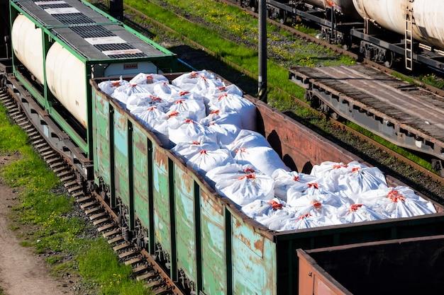 Перевозка удобрений в огромных мешках и вагонах по железной дороге. вагоны удобрений, товарный поезд.