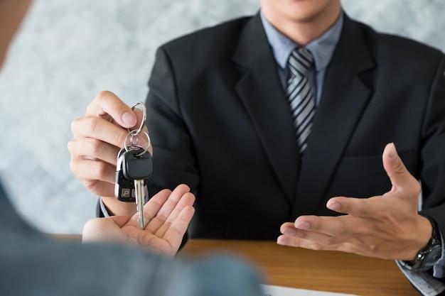 Trasporto e concetto di proprietà - cliente e venditore con chiave auto
