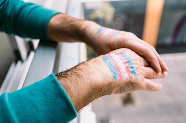 성전환자 남자는 난간에 그려진 성전환 깃발로 손을 얹습니다.