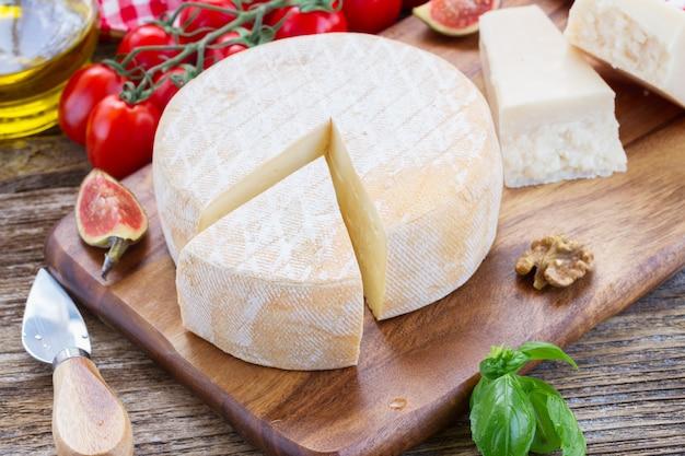 Сыр траппе на деревянной разделочной доске с помидорами черри