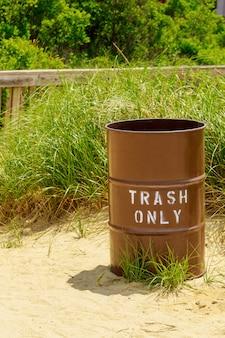 Trash can on hot sands of seaside