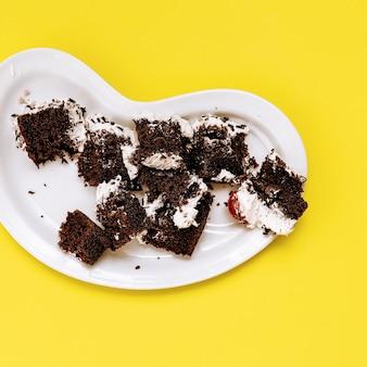 노란색 배경에 쓰레기 초콜릿 케이크입니다. 플랫 레이 푸드 바닐라 캔디 아트