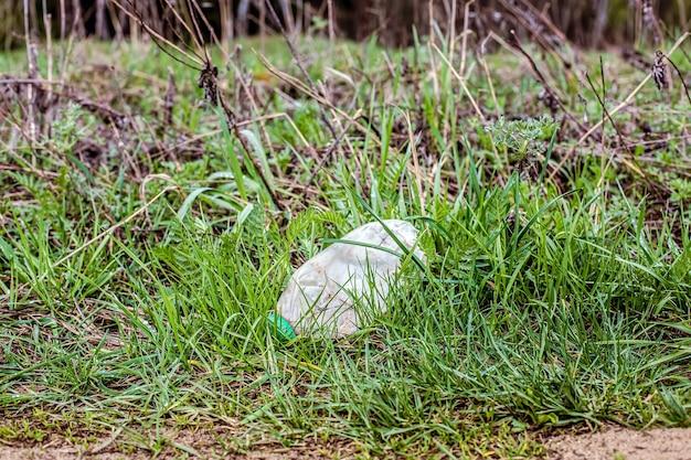 Пустая пластиковая бутылка для мусора лежит в зеленой траве в лесу. концепция экология и переработка