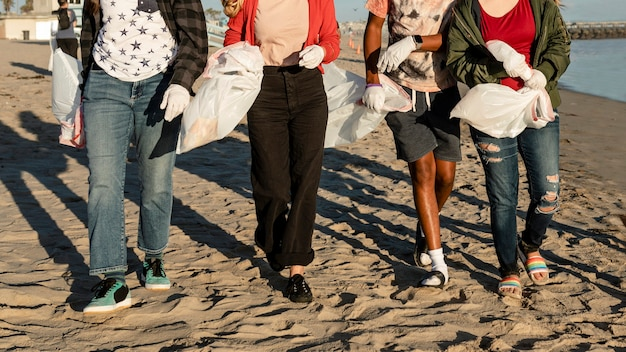 Trash pick up volunteering, group of teenagers at the beach