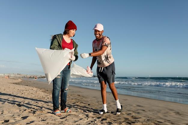 Волонтерство подбирает мусор, друзья-подростки на пляже