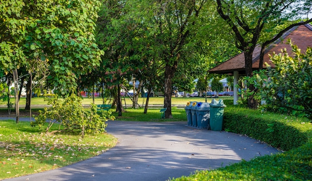 Trashcans in a park with green tree and plants in public park