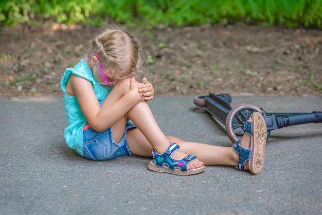 スクーターのトラウマ。 5歳の少女が公園のスクーターに転倒し、ひざをひどく傷つけました。電動スクーター傷害の概念。