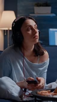 ソファの感触に一人で座っている電話で音楽を聞いているトラウマを抱えた欲求不満のストレスを感じて落ち込んでいる女性...