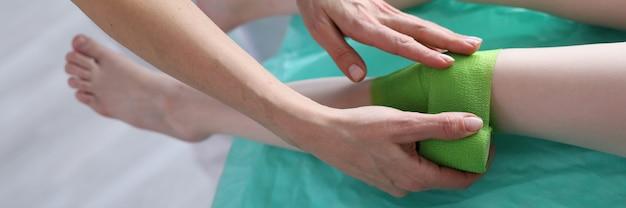 Traumatologist applies bandage to child injured leg