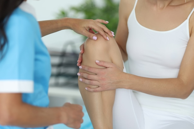 Врач травматолог осматривает колено пациента молодой женщины в белой одежде в клинике