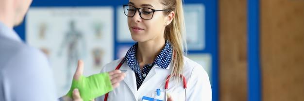 Травматолог осматривает пациента с травмами рук и растяжениями