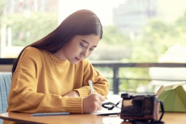 アジアの女性がメモに書いて、週末にtravalに行くことを計画して、一人でカフェに座っています。