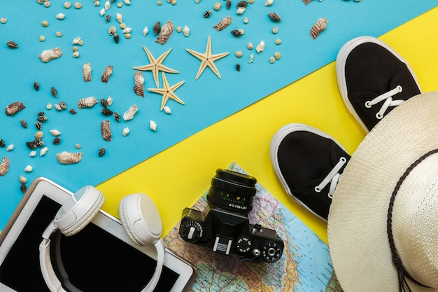Travel accessories camera, straw hat, card, shoes on a  yellow bluebackground flat top view layout with copy space