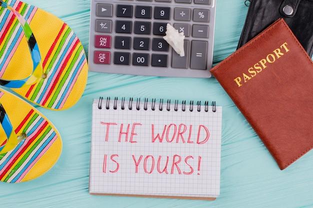 Концепция костюмов туристических аксессуаров для поездки в отпуск. паспорта, блокнот, шлепанцы на синем столе.