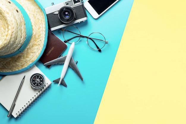 Travel accessories objects and gadgets top view flatlay on blue yellow pink background