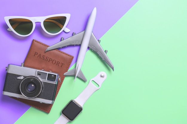 Travel accessories objects and gadgets top view flatlay on purple and teal