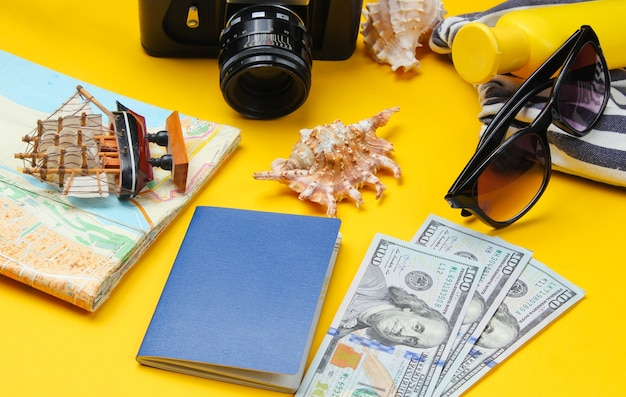 Travel accessories and retro camera on yellow, flat lay