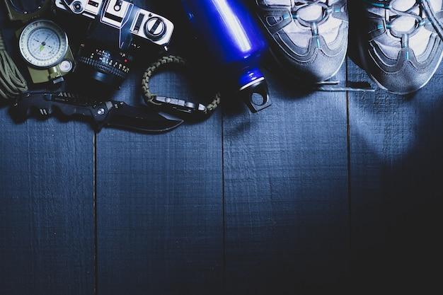 Дорожные аксессуары на черном деревянном фоне, синий походный ботинок