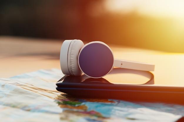 日当たりの良い表面のヘッドフォン、ラップトップ、地図にセットされたトラベルアクセサリー。旅行のコンセプト。旅行を集める。