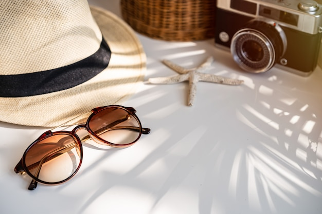 Travel accessories on the table with shadow of plam leave, summer vacation concept